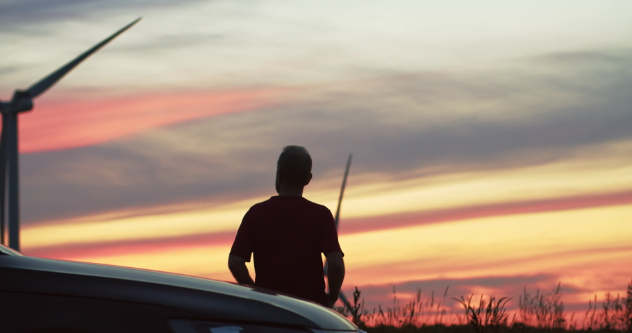 Inspired man standing by car observing large alternative power windmills spinning on pink sunset sky in the countryside.   Shutterstock HD Video #1035557594