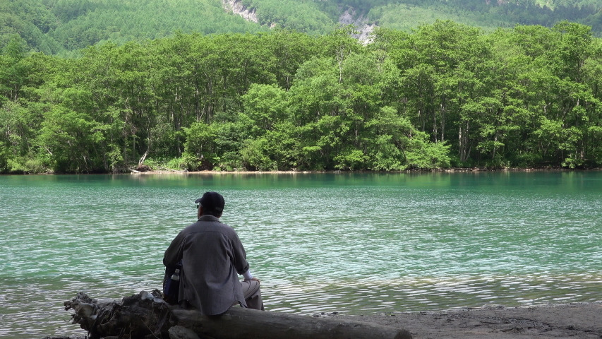 The old man sitting and relaxing by The beautiful Taisho Pond on summer in Kamikochi national park. | Shutterstock HD Video #1035559514