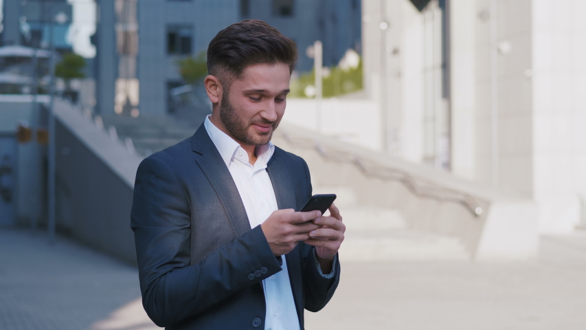 Businessman Using Smartphone and Reacting to Success. Handsome professional successful business man reaching personal goals. | Shutterstock HD Video #1035581054