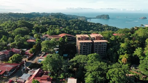 Drone Footage of Hotels and Buildings in Manuel Antonio Finca, Costa Rica Surrounded by Green Tropical Hills with the Pacific Ocean in the Background on a Sunny and Partly Cloudy Day