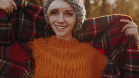 Young happy smiling tourist girl with orthodontic braces on her teeth, wears, wraps in red tartan scarf, enjoys sunny autumn in forest, park