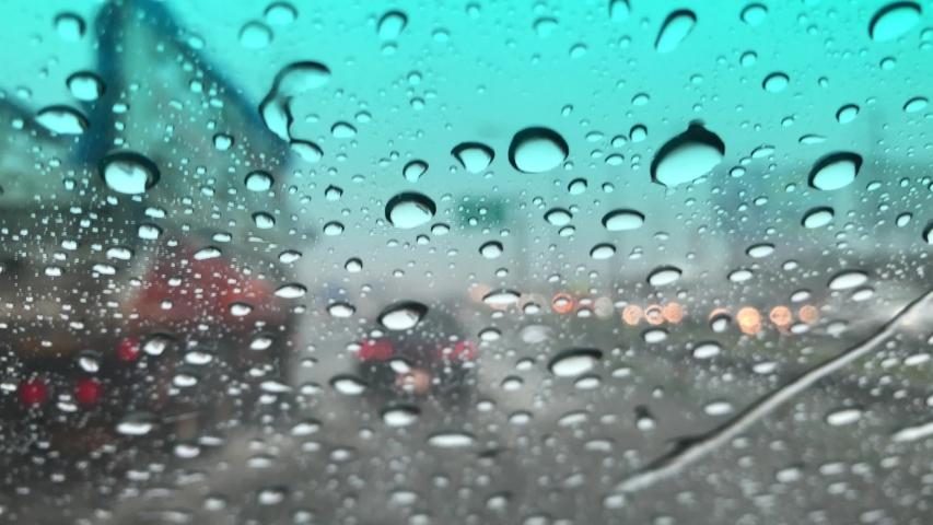 Movement of Rain falling on car windshield,drive car on street in city at heavy rain storm,blurred traffic light. | Shutterstock HD Video #1035703814