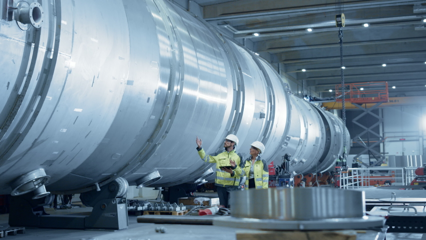 Two Heavy Industry Engineers Walking Through Pipe Manufacturing Facility, Use Digital Tablet, Have Discussion. Modern Industrial Design and Construction of Oil, Gas and Fuels Transport Pipeline | Shutterstock HD Video #1035704174