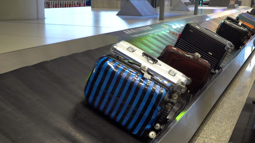 Various suitcases moving on the luggage conveyor belt at arrival area in the passenger terminal at Hong Kong International airport | Shutterstock HD Video #1035798914