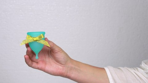 woman hands demonstrate a blue menstrual cup with gold bow as a bonus or gift, personal hygiene product at the time of menstruation