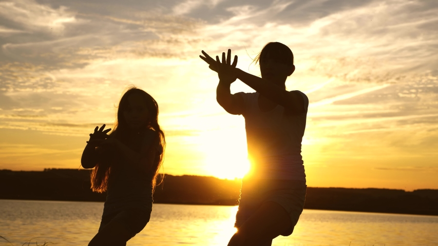 Teens girlfriends holiday disco. party by lake, children dancing. happy girls dancing on the beach. beautiful girls having fun listening to music. sisters are dancing.   Shutterstock HD Video #1035819464