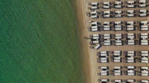 Aerial drone top down video of paradise organised mediterranean sandy beach with turquoise clear sea