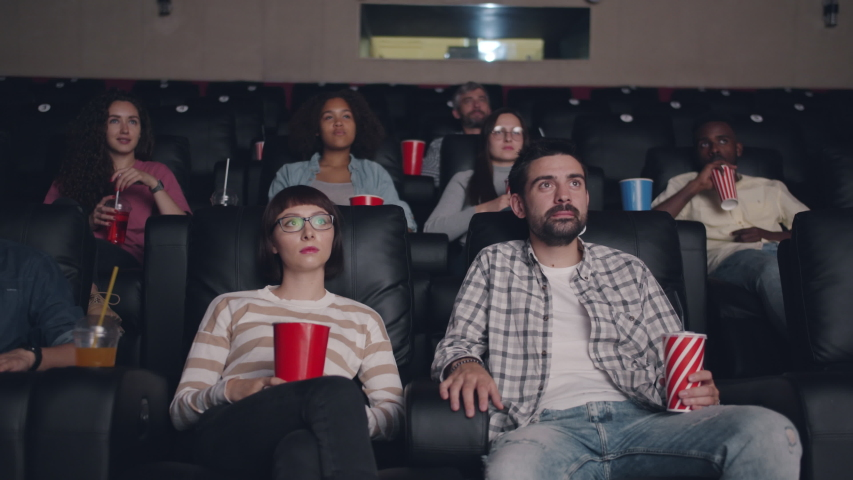 People young friends are watching film in cinema drinking and eating snacks sitting in darkness together enjoying movie. Youth and entertainment concept. | Shutterstock HD Video #1035872714