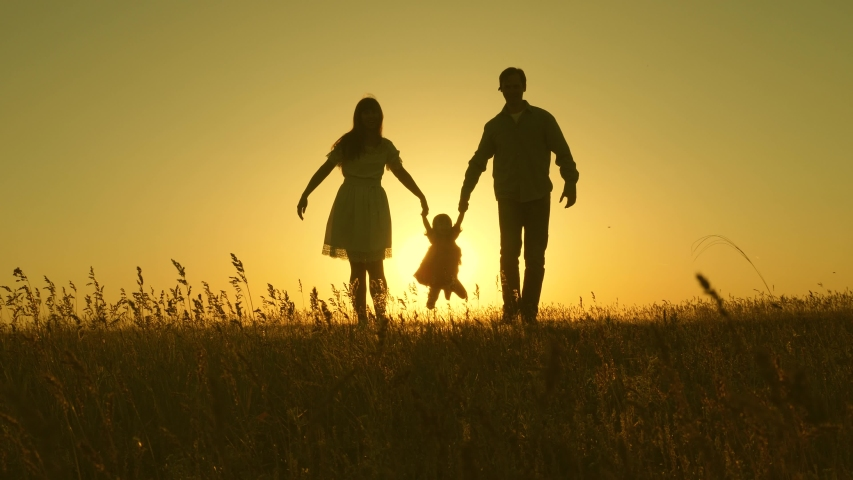 Little daughter jumping holding hands of dad and mom in park on background of sun. Family concept. child plays with dad and mom on field in sunset light. Walking with small kid in nature. | Shutterstock HD Video #1035882074
