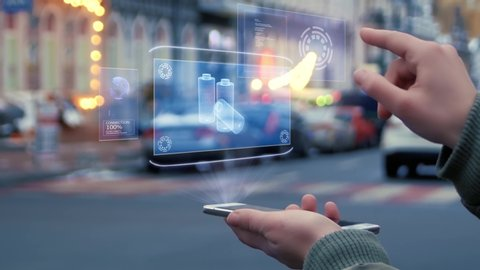 Female hands on the street interact with a HUD hologram with rechargeable batteries. Woman uses the holographic technology of the future in the smartphone screen on the background of the evening city