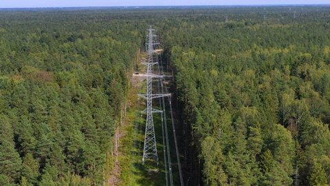 Tower of power lines in the forest. Electric tower line in Landscape view with Electricity and environmental problem concept. Ariel view High voltage power pylons.