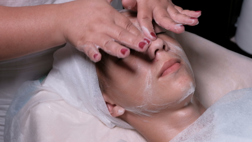 Beautician washes the boy's face with soapy foam. Teenager in beauty clinic. Male client gets facial cosmetology procedure in beauty salon. Medical face skin acne cleaning | Shutterstock HD Video #1036011734