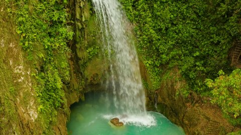 Waterfall in the rainforest jungle from above. Tropical Inambakan waterfalls in mountain jungle. Philippines, Cebu