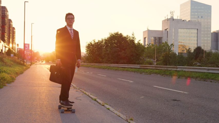 SLOW MOTION, LENS FLARE: Cool sporty businessman going home from work on his e-skateboard. Cheerful yuppie cruising through the city on a sunny summer evening. Happy young man enjoying his ride home.   Shutterstock HD Video #1036153754