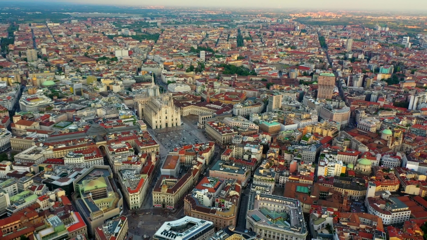 Duomo di Milano Cathedral, Aerial, reverse, drone shot, panning towards the church over buildings and architecture in the cityscape of Milan city, on a sunny evening, in Lombardy, Italy   Shutterstock HD Video #1036185194