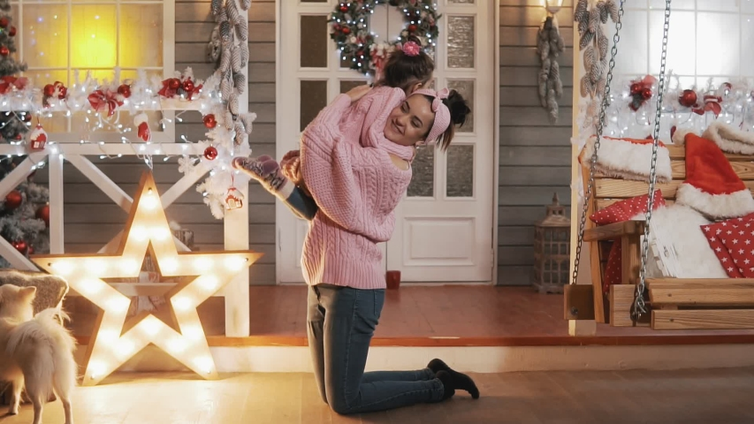 Beautiful mother and daughter in pink pullovers at Christmas day. Happy mother having fun with her kid daughter at Christmas porch. Mother tickling her little daughter in slow motion. Full length shot