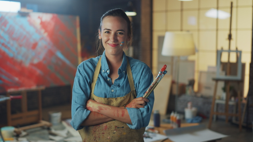 Professional Young Female Artist Dirty with Paint, Wearing Apron, Arms Crossed while Holding Brushes, Looks at the Camera with a Smile. Authentic Creative Studio with Large Canvas. Face Portrait | Shutterstock HD Video #1036269974