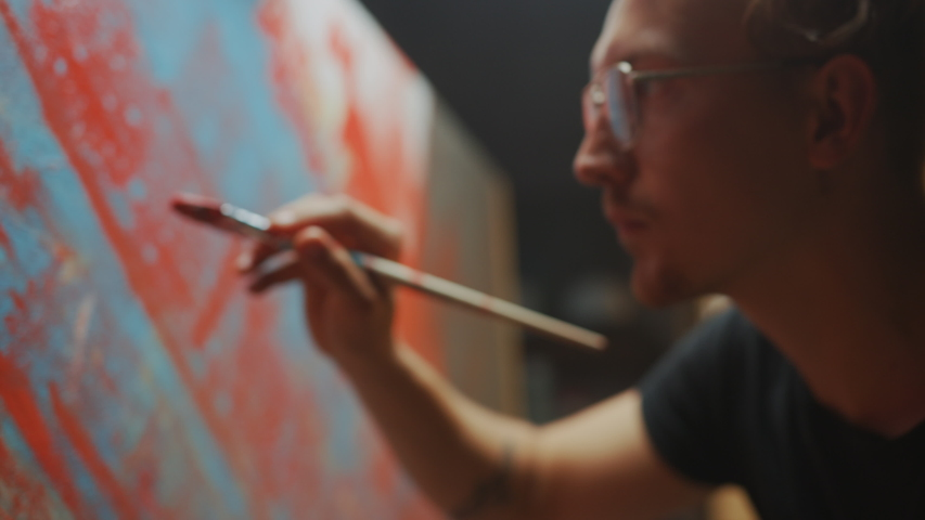 Portrait of Talented Artist Working on Abstract Painting, Uses Paint Brush To Create Daringly Emotional Modern Picture. Dark Creative Studio Large Canvas Stands on Easel. Side View Closeup Arc Shot | Shutterstock HD Video #1036270004