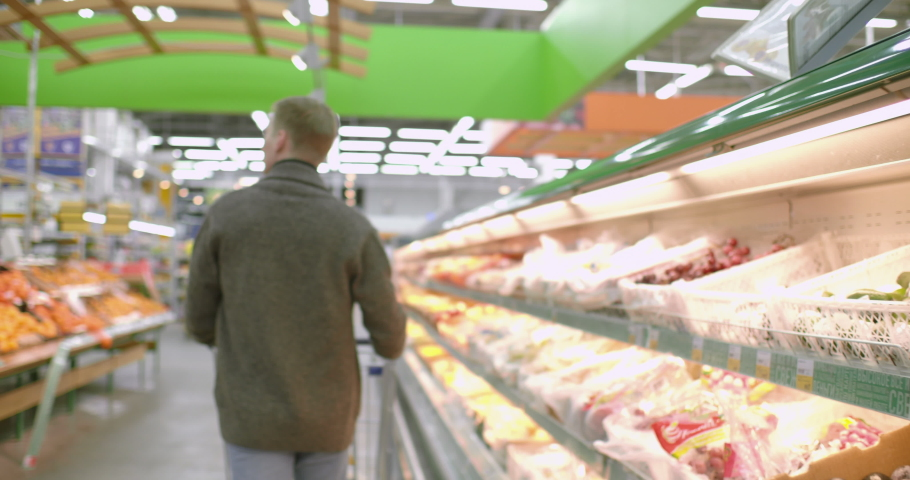 A man walks with a shopping cart in the fruit department of a supermarket. #1036351664