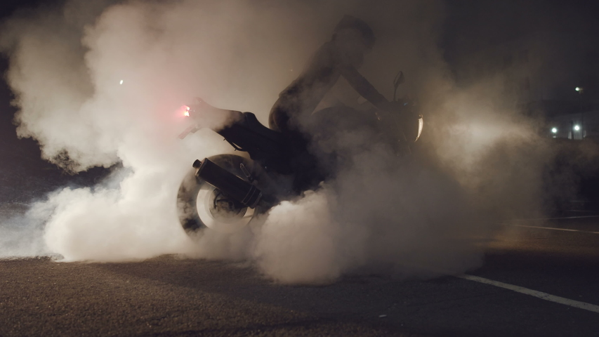 Rider in a black leather suit on a streetbike burning rubber. Slow motion. Smoke and sparks from under the wheels of a sport motobike. Night racing. Need for speed. | Shutterstock HD Video #1036379744