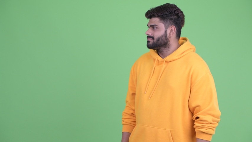 Happy young overweight bearded Indian man touching something and looking surprised | Shutterstock HD Video #1036384904