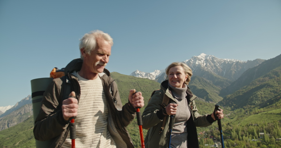 Mature caucasian couple on vacation, having a hike in spring mountains, spending time together after retirement together travelling - tourism, pension concept 4k #1036468094