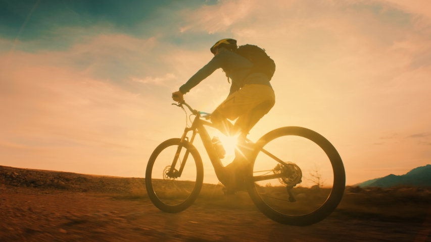 Low angle shot of a man cycling at sunset   Shutterstock HD Video #1036762574
