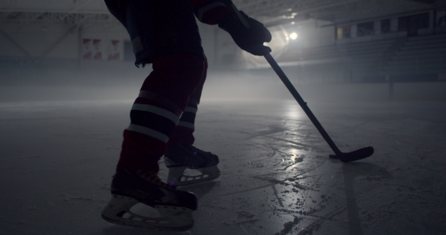 Hockey player starts skating in dramatically lit hockey rink skating and stick handling. Rink is filled with cool mist, fog in the air