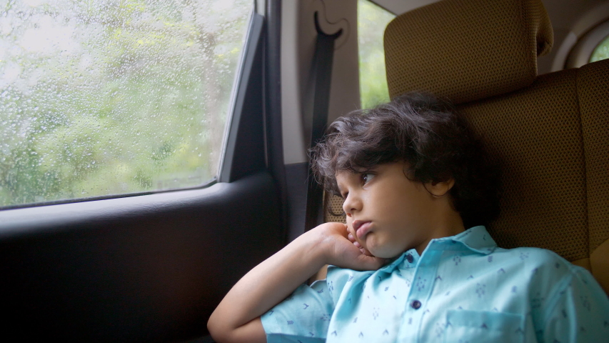 Tired little school kid traveling back home from long summer vacations in a car. Young Indian boy sitting alone in a car and looking outside the window in casual wear - unhappy, exhausted, sad child