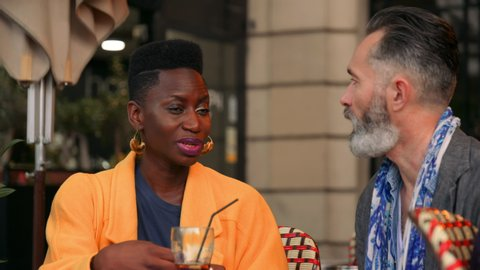 Beautiful Young Ethnic Woman Talks to her Older Boyfriend Over Dinner at an Outdoor Restaurant in France. Older Bearded Gentleman Converses with a Younger Stunning African-European Lady. 4K, slow mo.