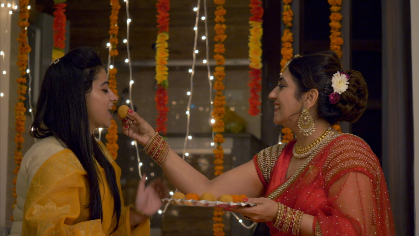 Happy Indian Family in colorful dress during Festive Season - Mother teasing and feeding ladoo to her daughter.   Shutterstock HD Video #1036932644