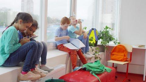 Handheld shot of male primary school teacher in glasses handing out workbooks to cute little children sitting on windowsill during break