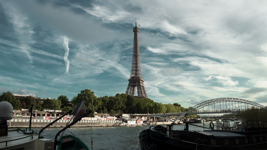 Eiffel Tower and river boats on the time lapse during rush hours in Paris, France. Summer cityscape, city life, vacation and touristic places in Europe. | Shutterstock HD Video #1036969004