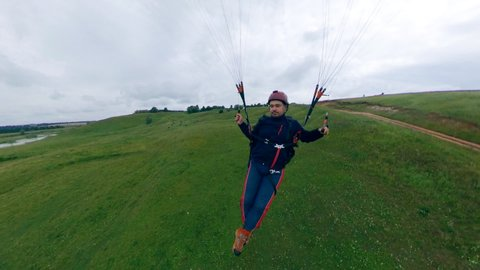 Sportsman training with a paraglider, flying over fields.