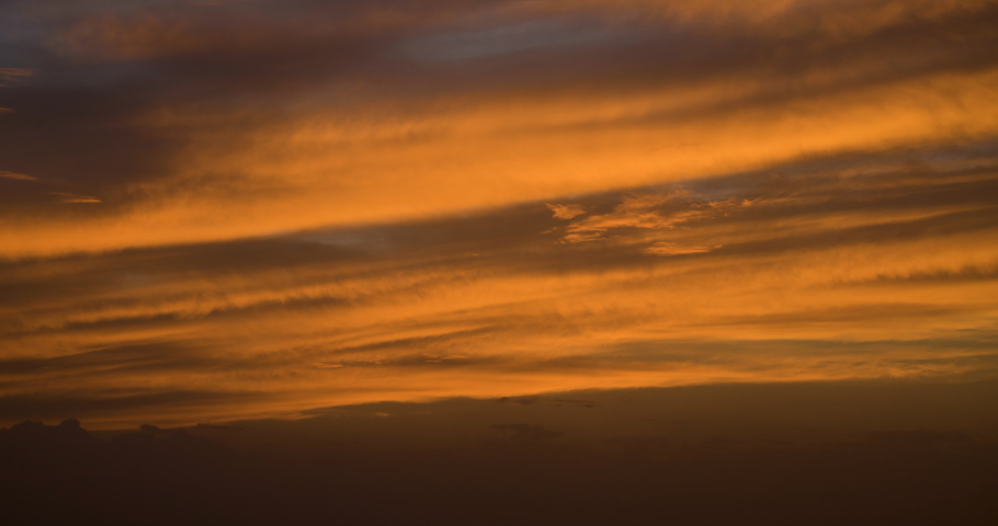 Orange and red sunset 4K time lapse with streamed and fast moving clouds in an overcast hazy desert. Oman.