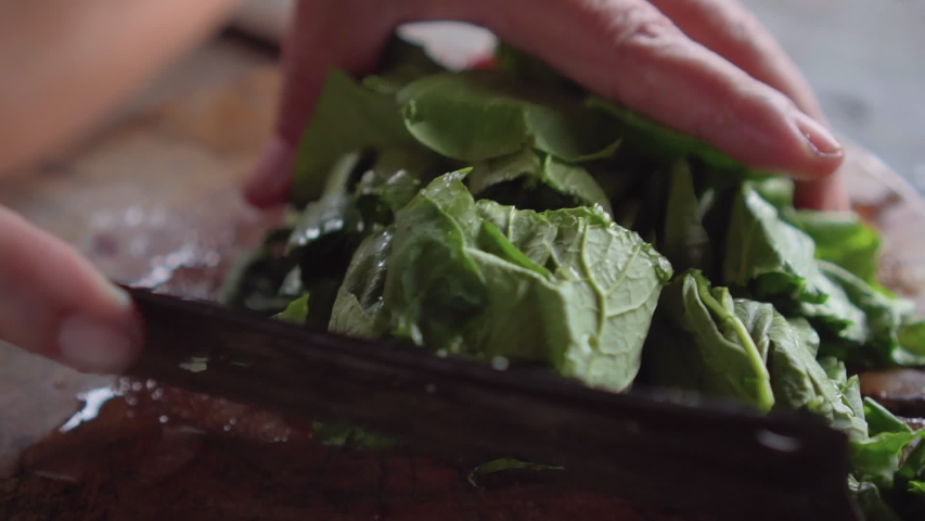 Chinese greens or yu choy get cutting on wooden board. preparing for vegetarian food. vegetarian festival. | Shutterstock HD Video #1037030594