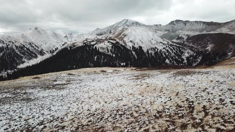 Aspen , Colorado / United States - 10 21 2018: Hikers Standing on Hill in Independence Pass of Rocky Mountains With Snow Covered Peaks in Autumn, Drone Aerial