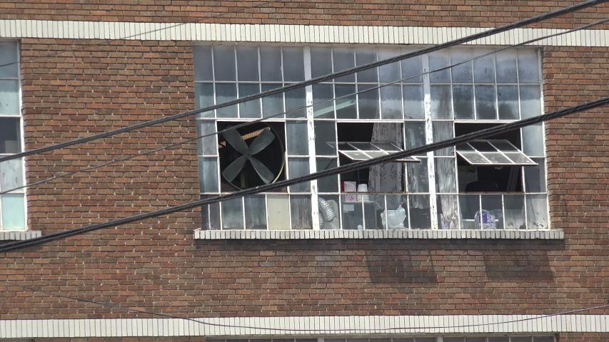 A window fan turning in an old warehouse window | Shutterstock HD Video #1037141234