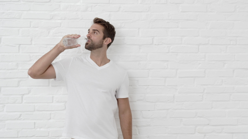 Handsome Guy Catching Water Bottle To Drink From, Smiling | Shutterstock HD Video #1037166284