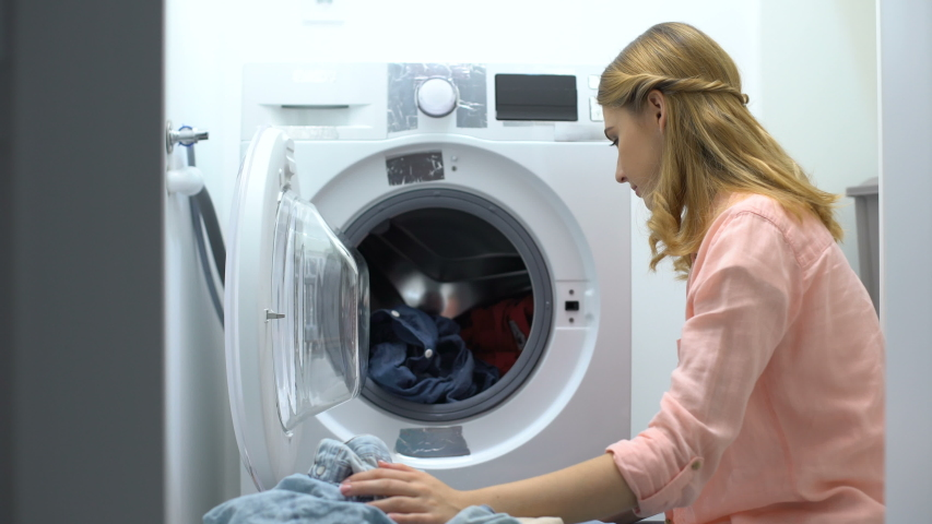 Woman sniffing clothes after washing, pleased with smell of soap-powder, laundry | Shutterstock HD Video #1037180804