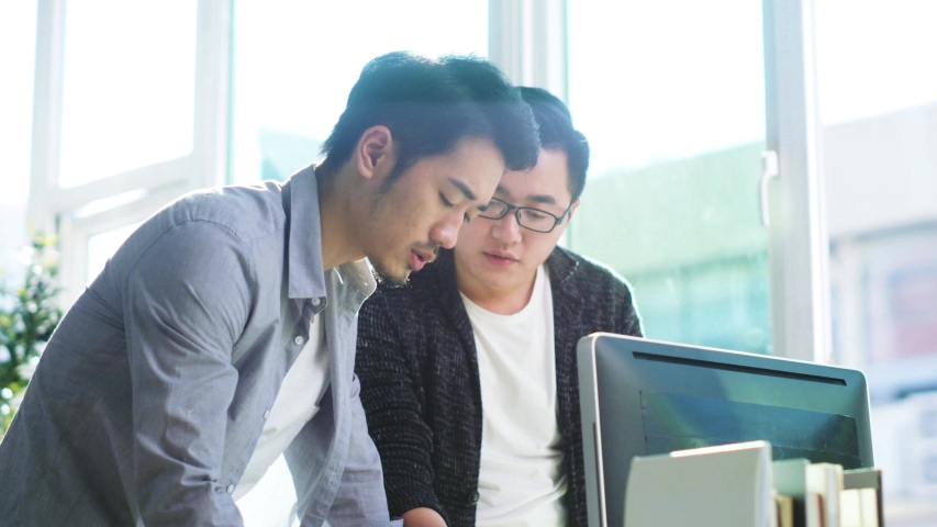 Two young asian entrepreneurs working together discussing business plans | Shutterstock HD Video #1037194694