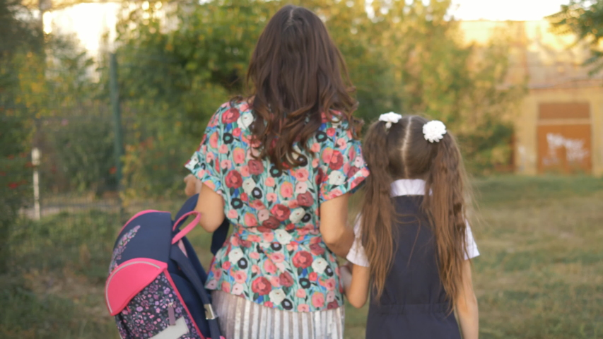 Mother and daughter go home from school after school. | Shutterstock HD Video #1037198804