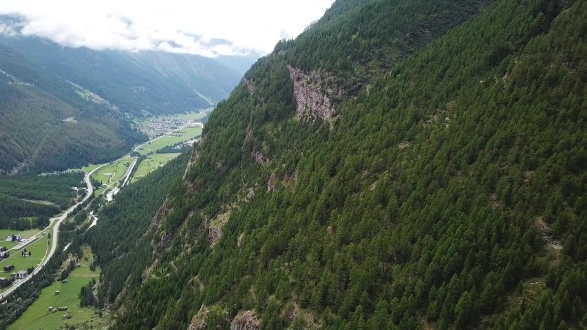 Scenic flight along a valley with green pine forest. drone flight along fir forest mountain on a cloudy day in randa wallis switzerland. | Shutterstock HD Video #1037220164