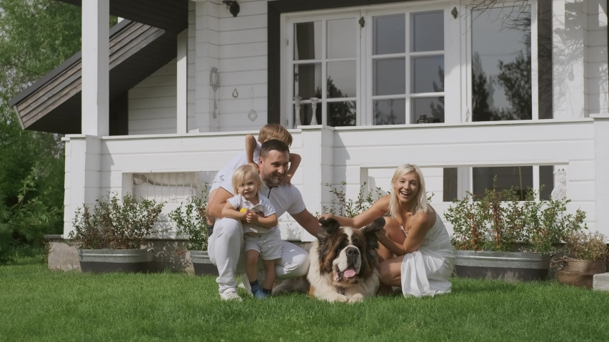 A young family of four in bright clothes and a dog have fun sitting near their white house   Shutterstock HD Video #1037236574