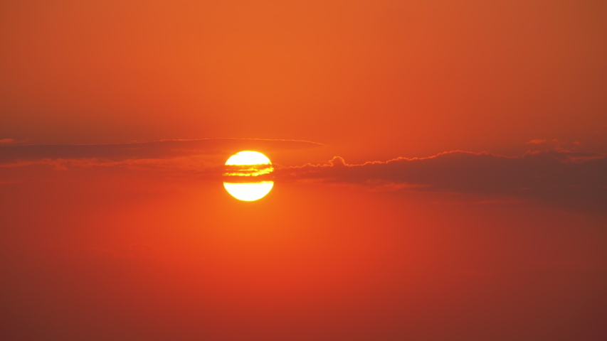 Sunset through the Clouds in the Red Sky. The orange sun sets smoothly down. Colorful sunset in summer. Real time. 4K