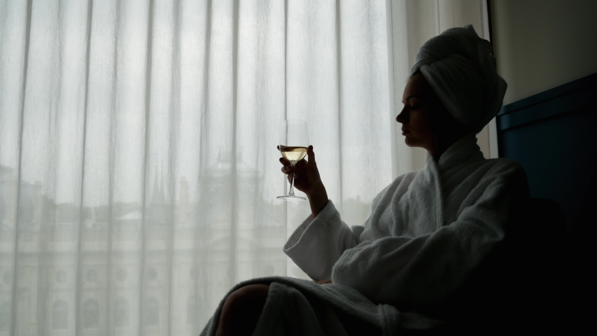 Silhouette of elegant woman in a white bathrobe and a towel on her head enjoying of glass of white wine in hotel room | Shutterstock HD Video #1037298374