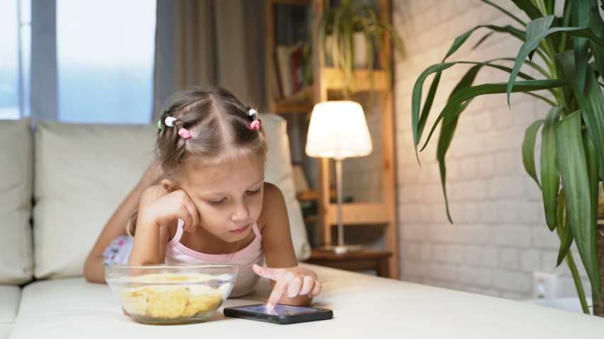 Little Girl Child Home On Sofa Playing On Smartphone   Shutterstock HD Video #1037314544