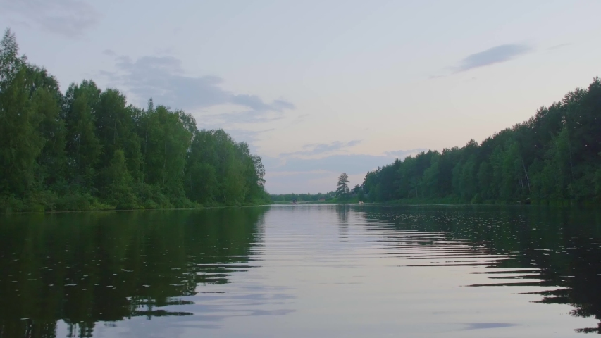 Smooth movement of the camera over the water of a small lake surrounded by many trees | Shutterstock HD Video #1037361914