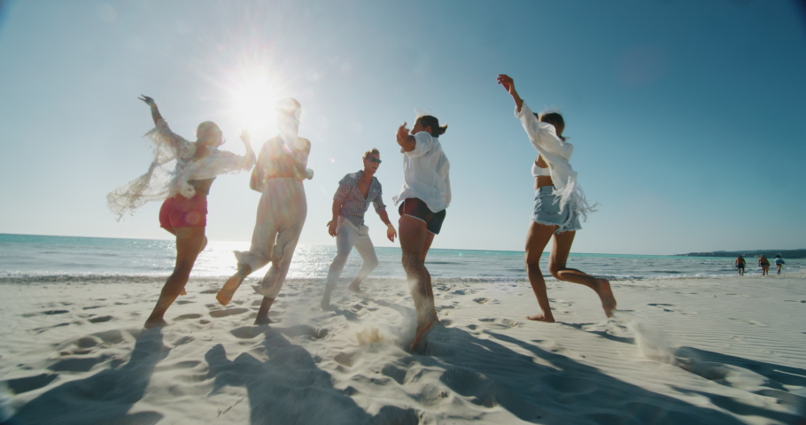 Slow motion of young multi-ethnic friends  are having fun to enjoy their summer vacation together on a beach with a sea in a sunny day. #1037398754