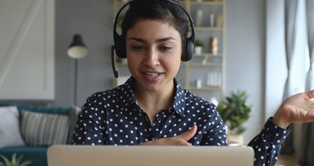 Happy indian young woman wear headset communicating by conference call speak looking at computer at home office, video chat job interview or distance language course class with online teacher concept